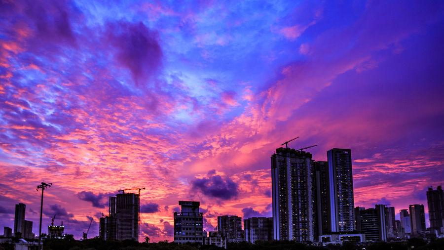 Modern buildings against sky during sunset