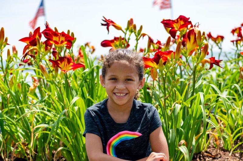 Portrait of smiling girl against flowering plants