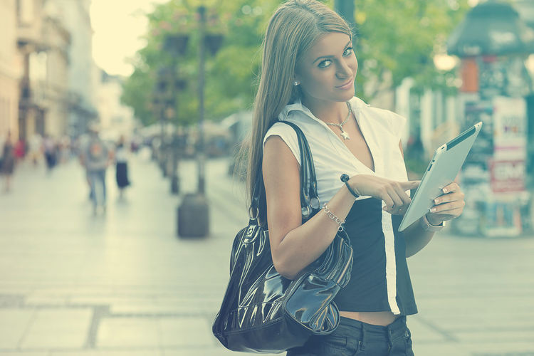 Portrait Of Young Woman Using Digital Tablet While Standing On City Street