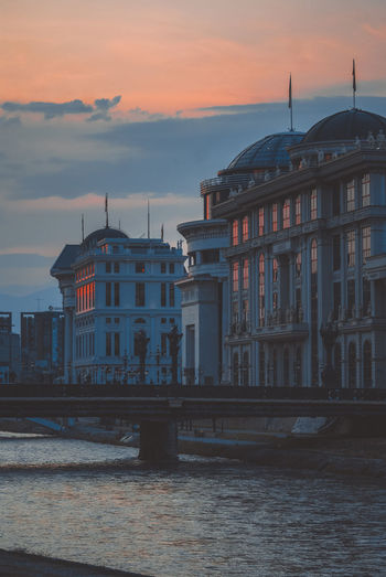 Bridge over river against buildings in city during sunset