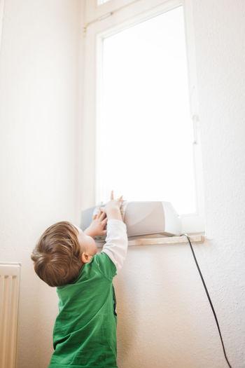 Boy touching radio on window