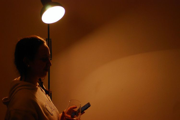 Woman using mobile phone by lamp at home