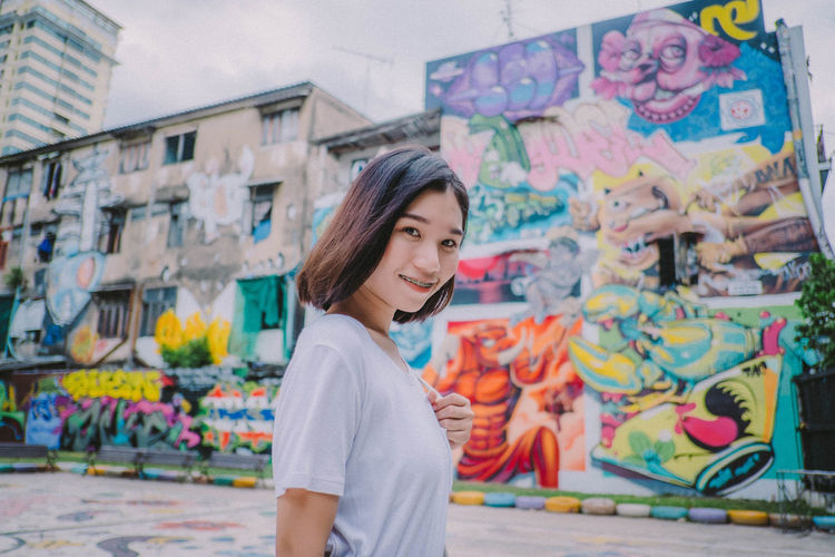Portrait of smiling young woman standing against graffiti wall