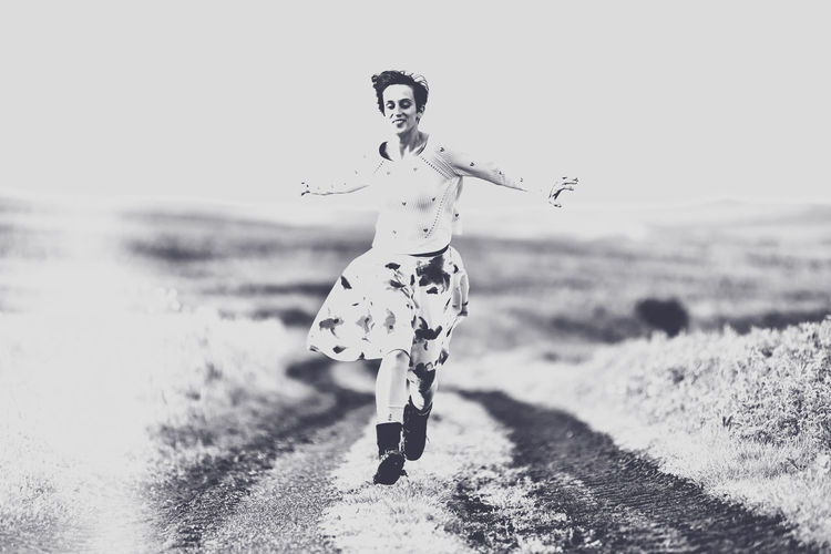 Woman Running On Dirt Road Against Clear Sky