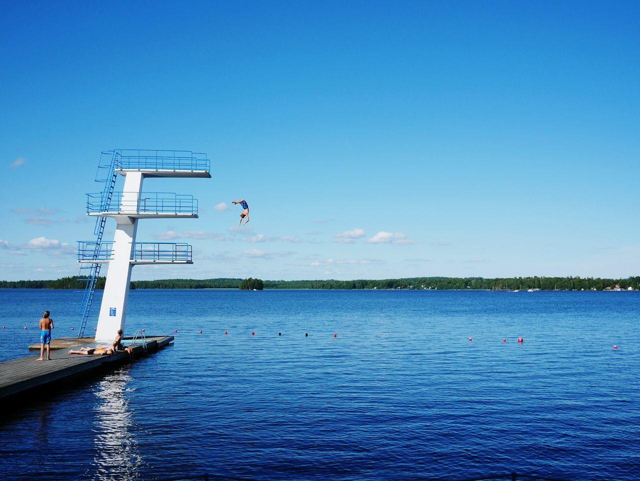 Man diving off high platform into lake