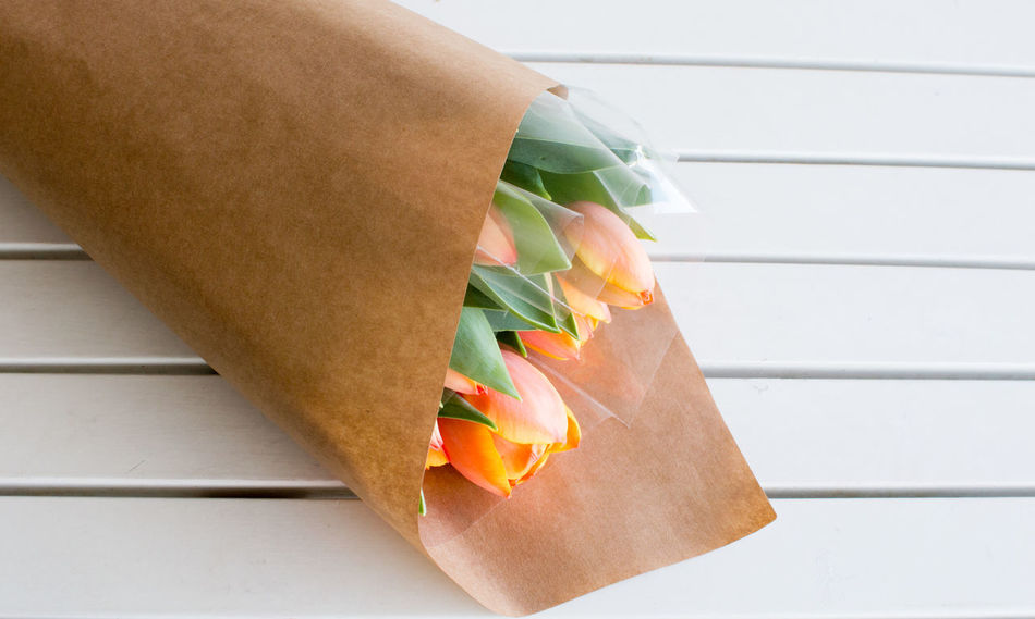 Orange tulips in brown paper Orange Tulips Bag Beauty Bouquet Close-up Day Focus On Foreground Freshness Gift Indoors  Paper Paper Bag Still Life
