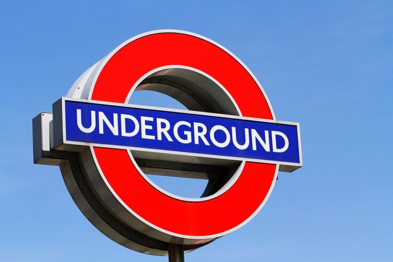 Low Angle View Of London Underground Sign Against Blue Sky