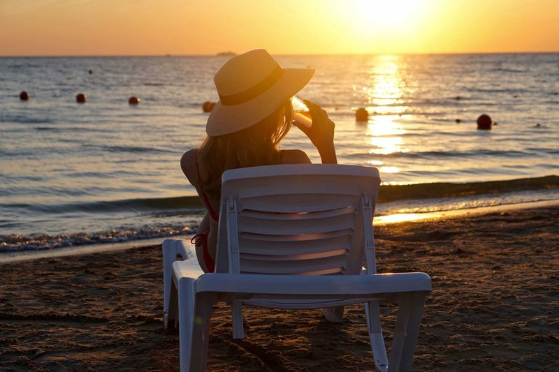 Rear view of woman having drink on lounge chair at beach during sunset
