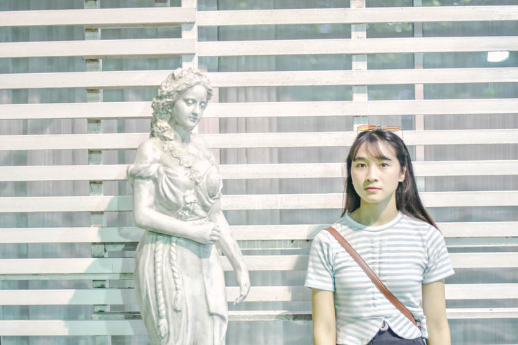 Portrait of young woman standing against sculpture by window outdoors