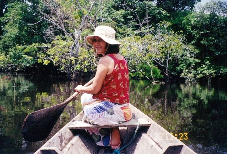 Woman sitting on boat against lake
