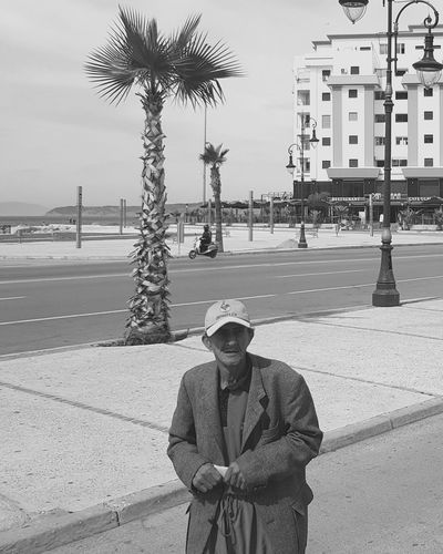 Portrait of man standing by palm tree in city