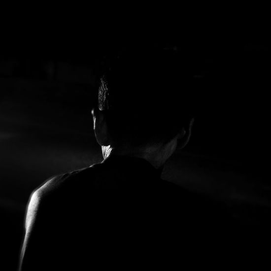 Rear view of man against black background