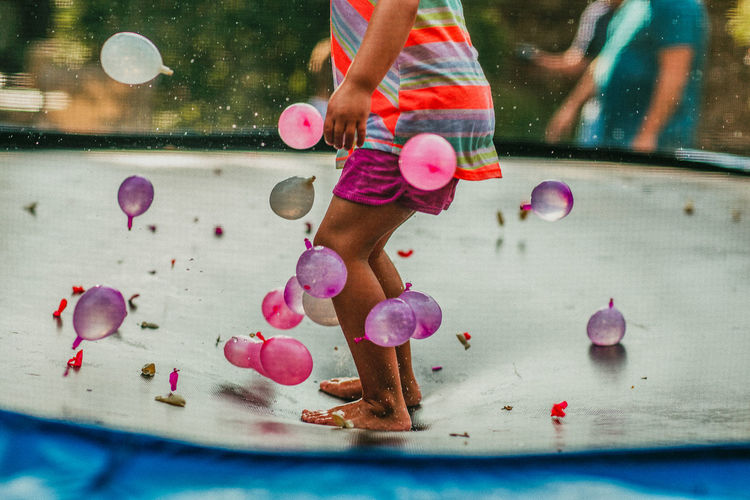 child jumping on trampoline with water balloons