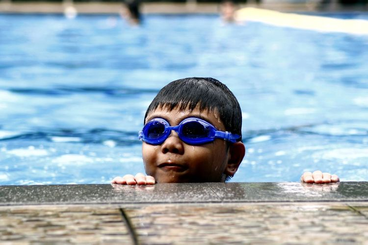 Boy Wearing Swimming Goggles At Pool