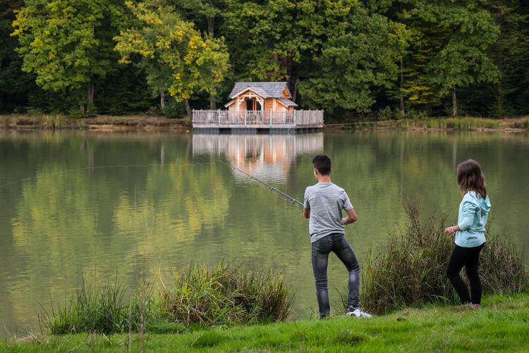 Rear View Of Boy Fishing At Riverbank