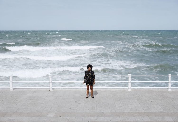 Woman Standing Against Sea In Sunny Day