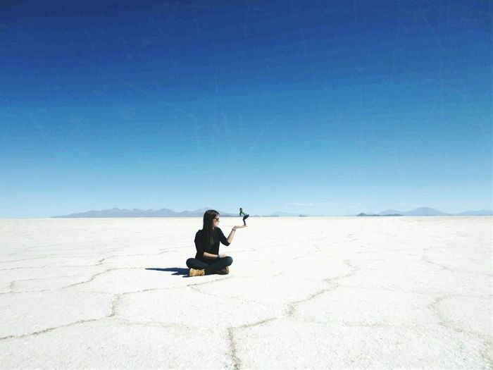 Optical Illusion Of Woman Holding Friend At Salar De Uyuni Against Sky