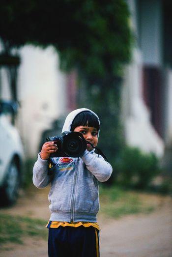 Portrait Of Boy Holding Camera On Street