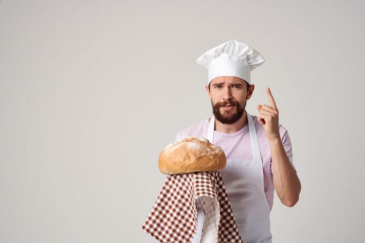 Portrait of man holding ice cream against white background