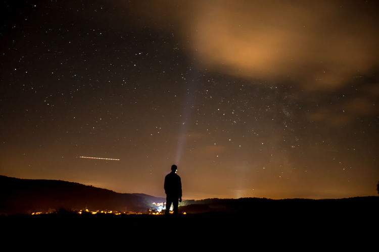 Rear view of man standing on mountain at night