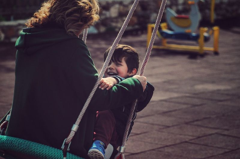 Grandmother And Grandson Enjoying Swing At Playground