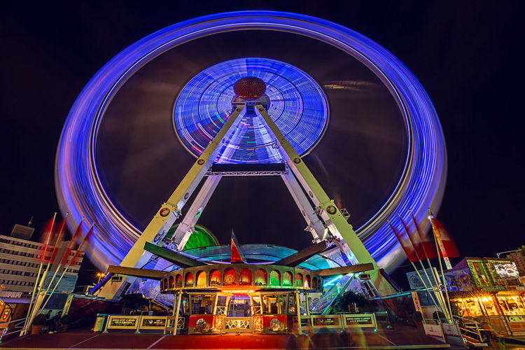 Hamburg Hamburger Dom Amusement Park Amusement Park Ride Architecture Arts Culture And Entertainment Blue Building Exterior Built Structure Carnival Circle City Fairground Ferris Wheel Geometric Shape Illuminated Low Angle View Night Nightlife No People Outdoors Sky Spinning Travel Destinations
