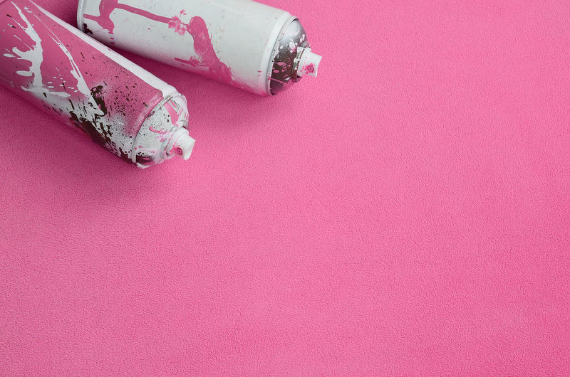 High angle view of spray bottles on pink background