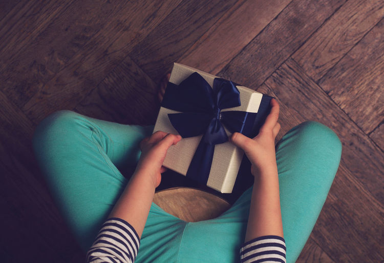 Low Section Of Girl Holding Gift Box While Sitting On Hardwood Floor