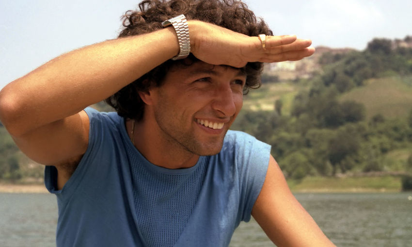 Close-up of smiling young man shielding eyes