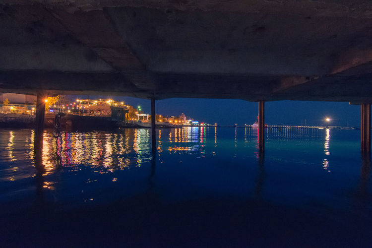 Reflection Of Illuminated Built Structure In Sea At Night