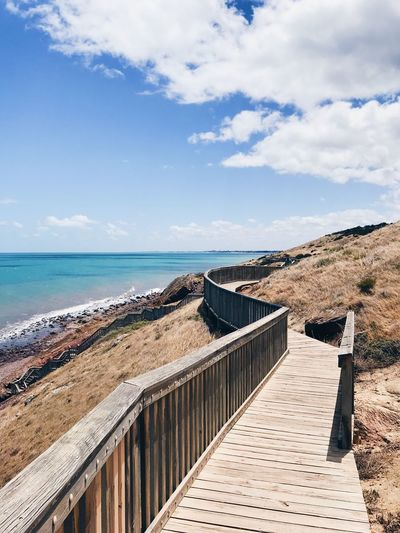 Boardwalk on cliff by sea against sky