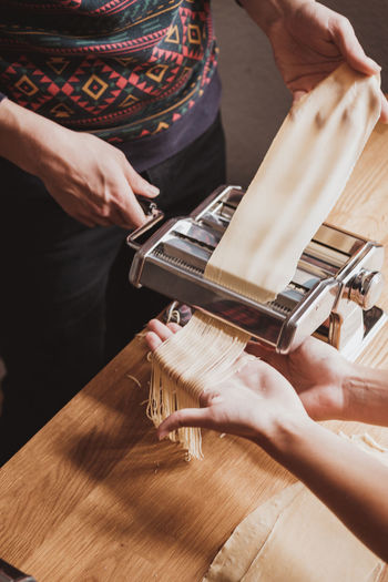 Cropped image of women preparing pasta with machine in kitchen