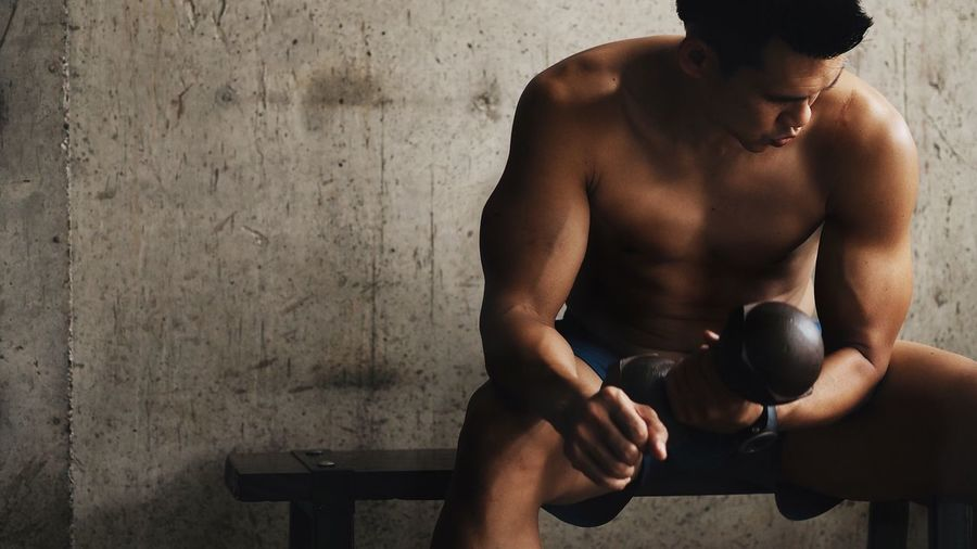 Shirtless man holding dumbbell while sitting in gym