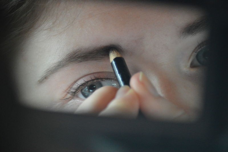 Cropped image of woman applying eyebrow pencil while reflecting on mirror