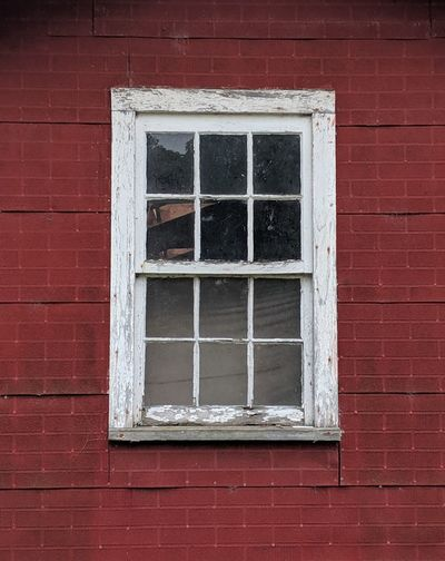 Low angle view of window on brick wall of building