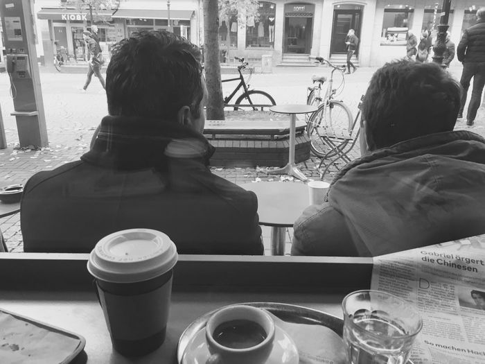Rear view of man and woman sitting at cafe