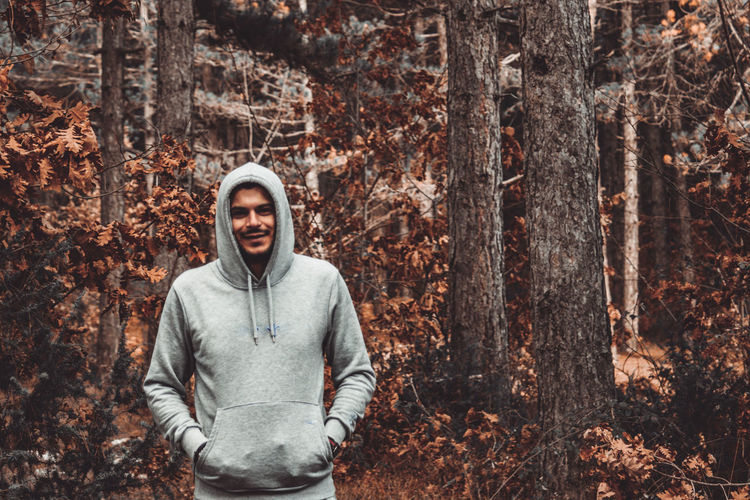 Portrait of smiling man standing by tree trunk in forest