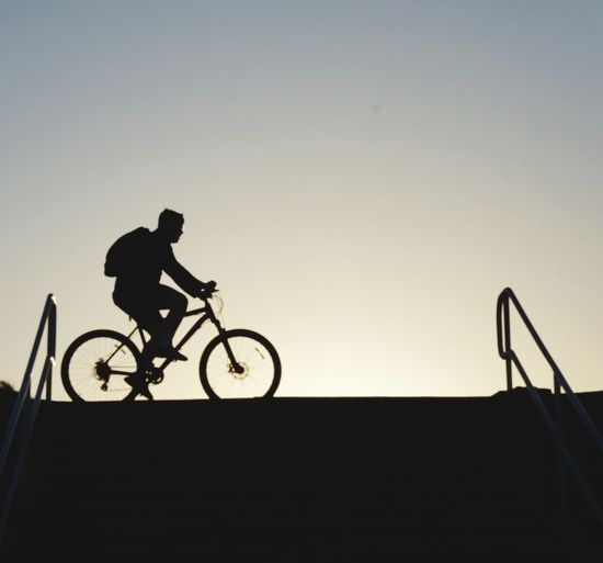 Silhouette man riding bicycle against clear sky