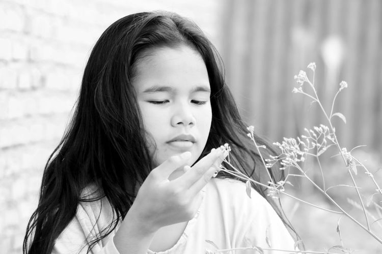 Girl looking at flowering plant in lawn