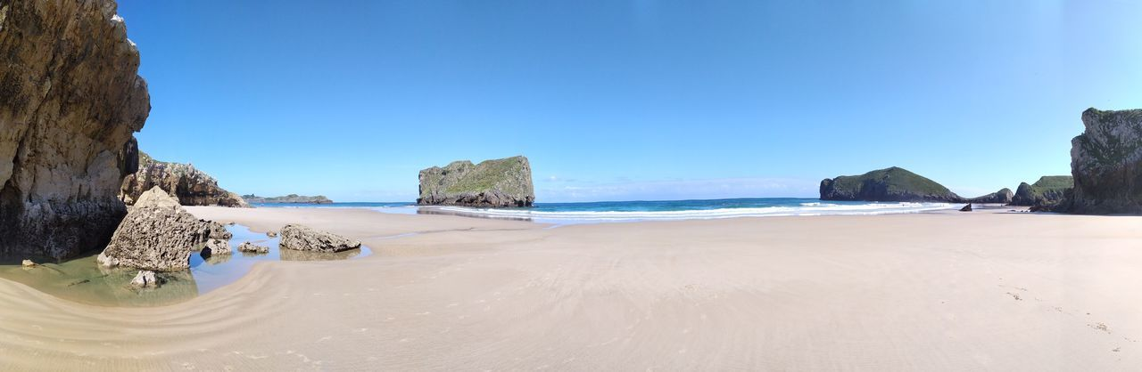 Panoramic view of beach against clear blue sky