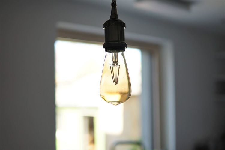 Low angle view of light bulb hanging from ceiling
