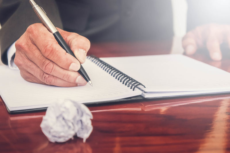 Businessman Writing In Diary On Table At Office