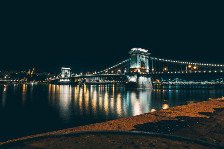 Illuminated chain bridge over river danube against clear sky at night