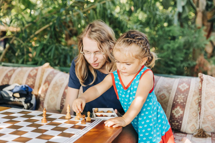 Girl playing chess with father