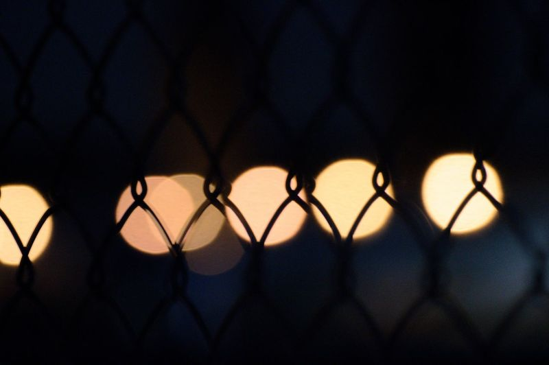 Close-up of silhouette chainlink fence against lens flare