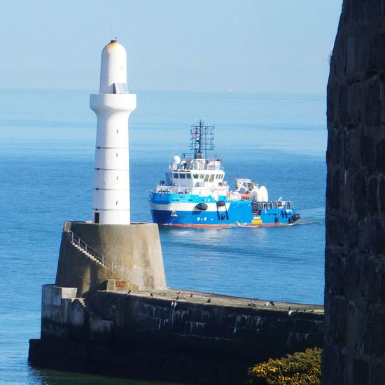 Boat Sailing By Lighthouse