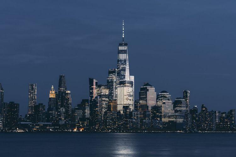 Illuminated buildings in city against sky in new york city manhattan