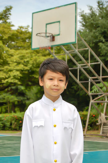 Portrait of a boy wearing white clothes, basketball court. Basketball - Sport Boys Child Childhood Day Front View Innocence Leisure Activity Lifestyles Looking At Camera Males  Men One Person Outdoors Portrait Real People Sport Standing Tree Waist Up
