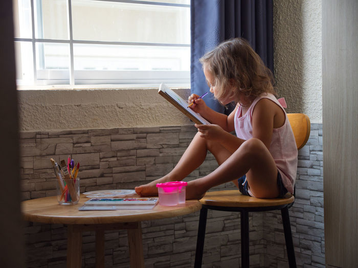 Side view of girl drawing on paper while sitting on chair at home