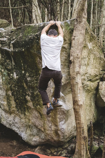 Full length of man on rock against trees